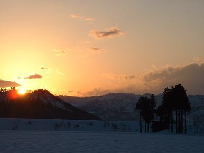 魚沼産コシヒカリの田んぼの向こうに沈む夕日